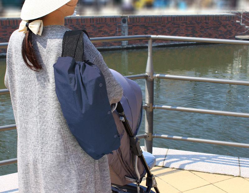 ネイビーの抱っこ紐カバーを肩掛け。川沿いの散歩道