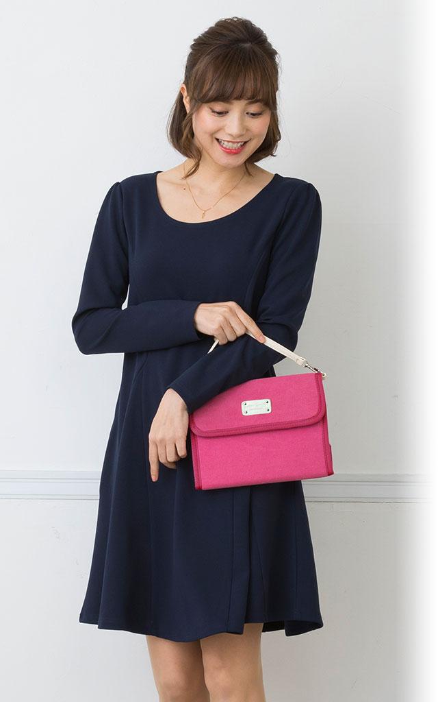 ピンクの母子手帳ケース、ストラップを腕に掛けたモデルイメージ