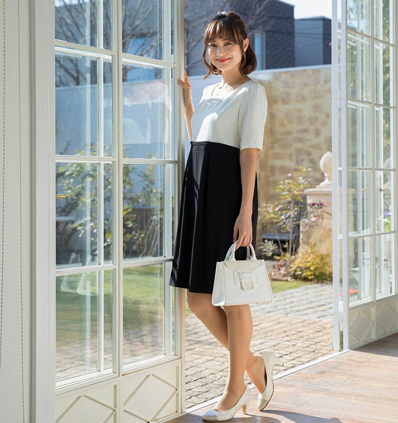 オフホワイト×ブラックの清楚な授乳フォーマル 窓辺に立つモデルイメージ